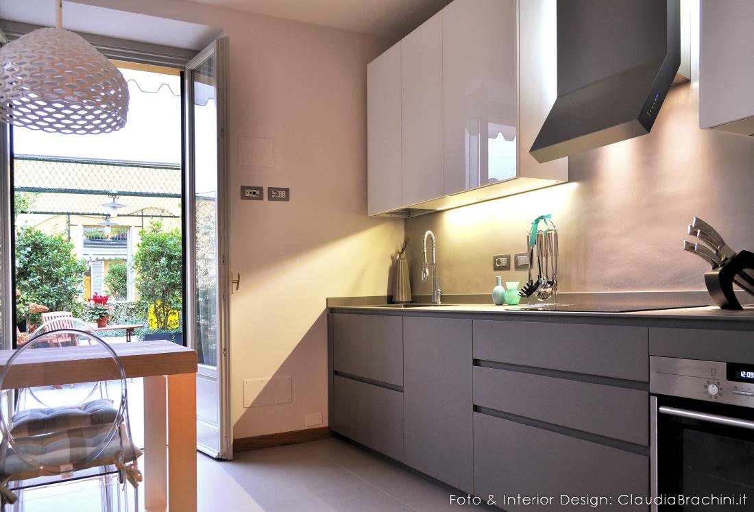 cucina in resina di cemento con gola e pensili in vetro