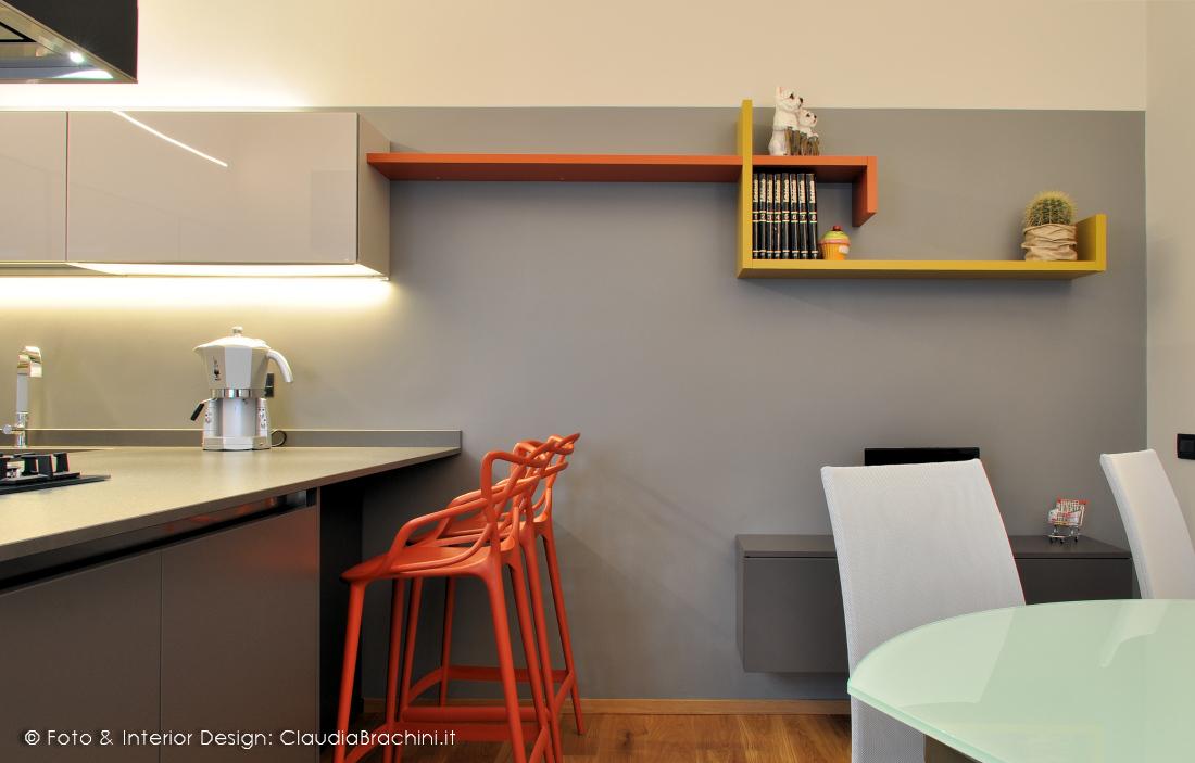 cucina grigia in vetro con particolari arancio