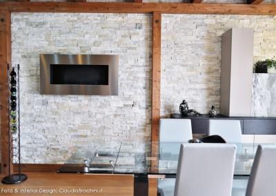 soggiorno con parete in geopietra e biocamino
