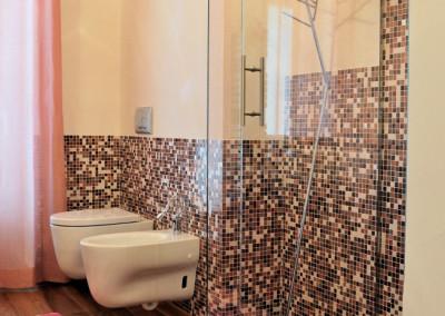 bagno mansardato mosaico rosa e fucsia