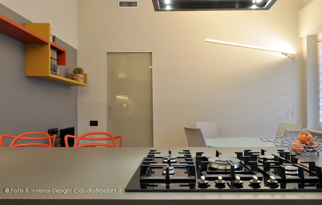 cucina grigio con particolari arancio, grande penisola con sgabelli