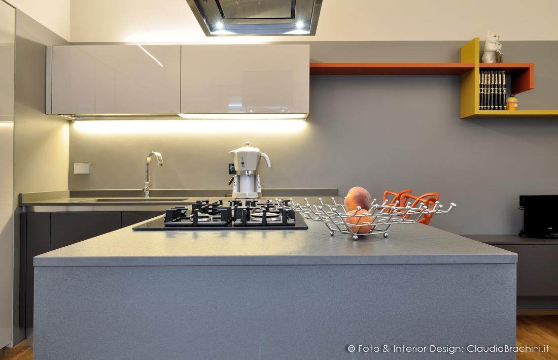 cucina grigio in vetro con particolari arancio, grande penisola con sgabelli