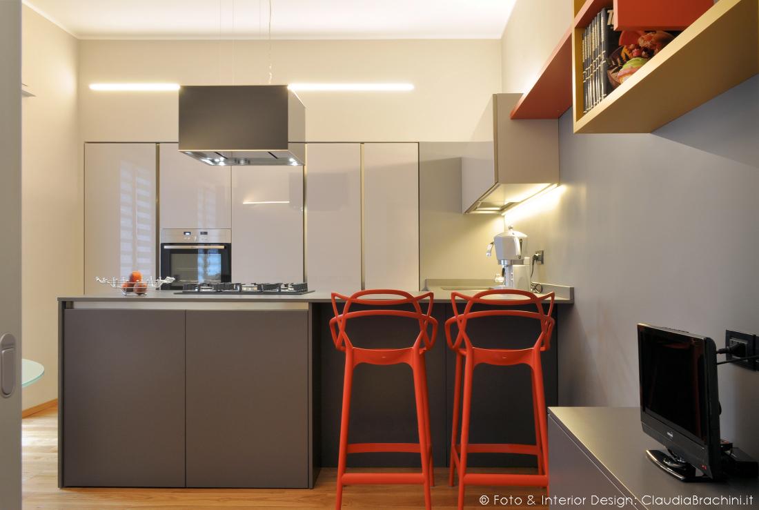 cucina grigia in vetro con particolari arancio grande penisola con sgabelli