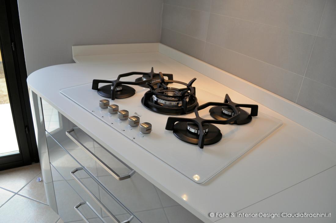 cucina laccata lucida bianca e grigio con elementi curvi, piano cottura in vetro bianco