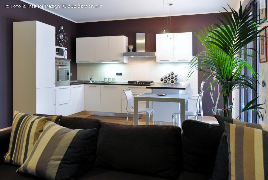 soggiorno living cucina bianca con penisola e parete cacao