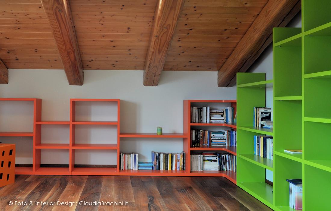 libreria a gradoni arancio e verde in mansarda